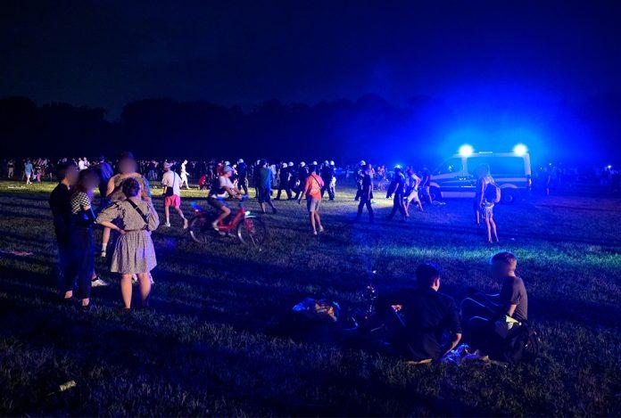 Hamburger Stadtpark in der Nacht mit vielen Menschen wird von der Polizei geräumt