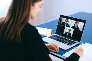Junge Frau vor ihrem Computer in einem Zoom-Meeting