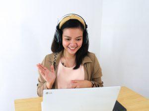 Frau winkend vor ihrem Laptop mit Kopfhörern auf