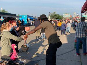 Jesse Greaves grüßt eine Kundin auf dem Fischmarkt.