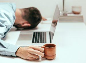 Mann liegt mit dem Kopf auf dem Tisch, vor ihm sein Laptop, in der Hand eine Kaffee Tasse
